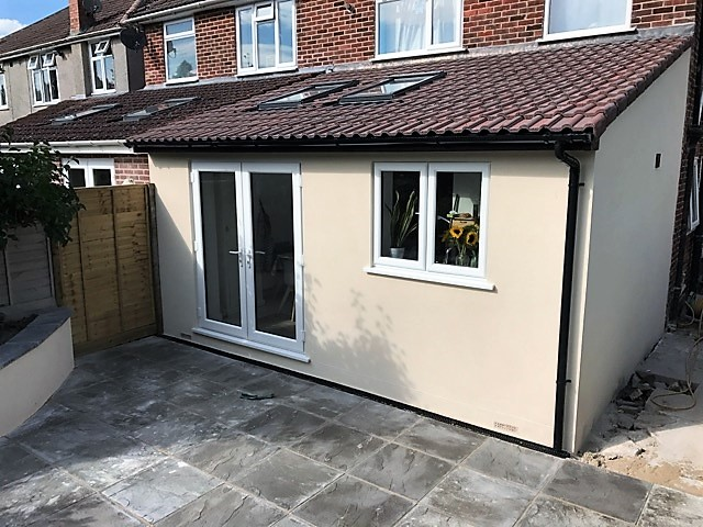Rear extension with kitchen and new patio with retaining garden wall
